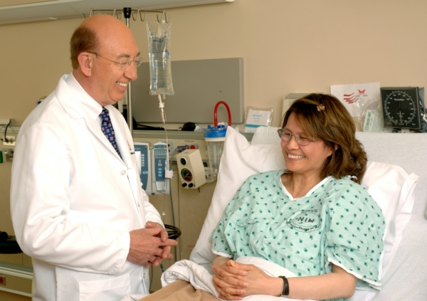 A doctor at the National Cancer Institute talking with a patient in a hospital bed.